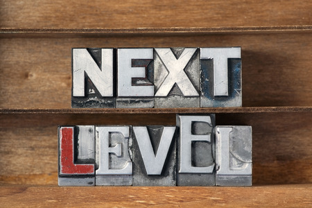letterpress type: next level made from metallic letterpress type on wooden tray Stock Photo