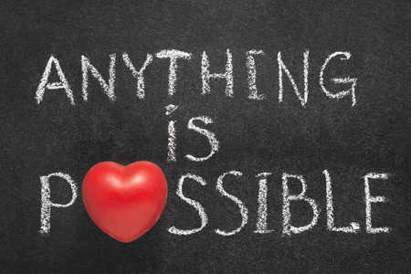 anything: anything is possible phrase handwritten on chalkboard with heart symbol instead of O
