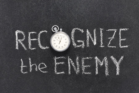 recognize: recognize the enemy phrase handwritten on chalkboard with vintage precise stopwatch used instead of O
