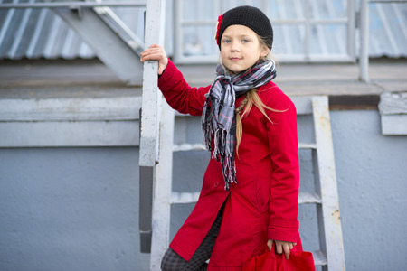 metallic stairs: girl in red raincoat on urban metallic stairs