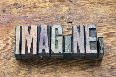 letterpress type: imagine word made from wooden letterpress type on grunge wood