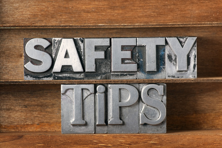 safety tips phrase made from metallic letterpress type on wooden tray