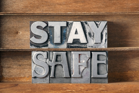 stay safe phrase made from metallic letterpress type on wooden tray