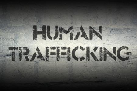 trafficking: human trafficking stencil print on the grunge white brick wall
