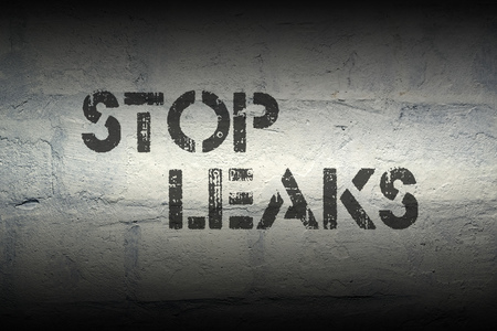 safety slogan: stop leaks stencil print on the grunge white brick wall