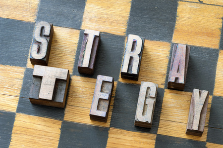 letterpress type: strategy word made from letterpress wooden type on vintage chessboard Stock Photo