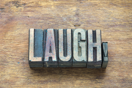 letterpress type: laugh word made from wooden letterpress type on grunge wood Stock Photo