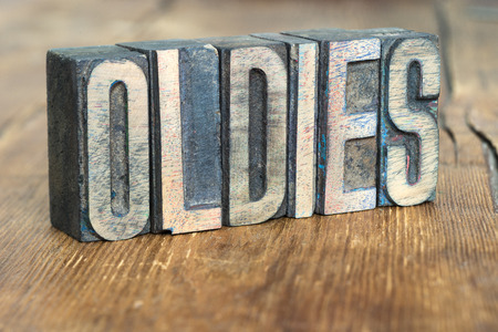 letterpress type: oldies word made from wooden letterpress type on grunge wood Stock Photo