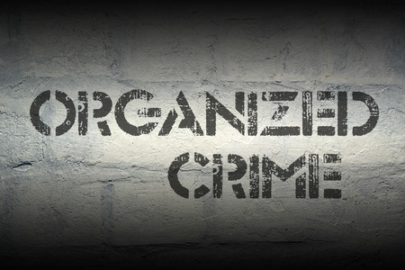 syndicate: organized crime stencil print on the grunge white brick wall