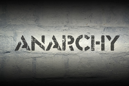 anarchism: anarchy stencil print on the grunge white brick wall