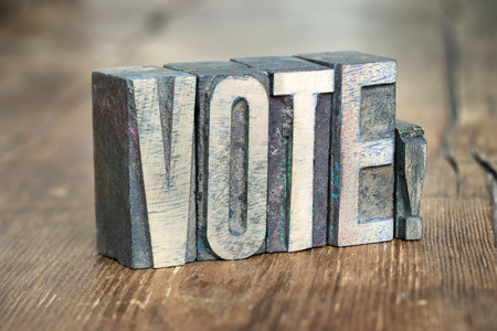 letterpress type: vote exclamation made from wooden letterpress type on grunge wood