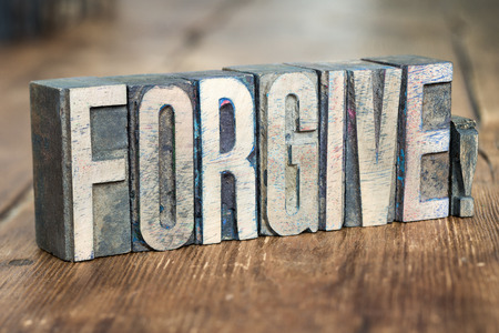 remit: forgive exclamation made from wooden letterpress type on grunge wood
