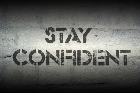 to stay: stay confident stencil print on the grunge white brick wall Stock Photo