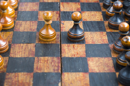 two minds: vintage wooden black and white pawn pieces in opposition at game start on chessboard