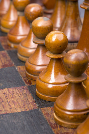 pawns: row of vintage wooden pawns on chessboard with focus on second piece Stock Photo