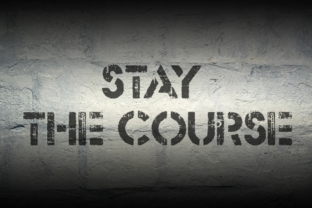 stay on course: stay the course stencil print on the grunge white brick wall