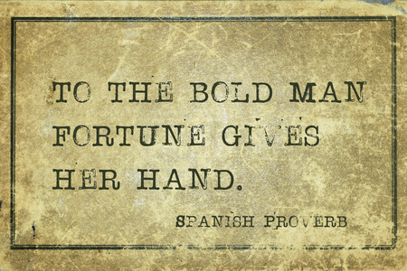 proverb: To the bold man fortune gives her hand - ancient Spanish proverb printed on grunge vintage cardboard Stock Photo