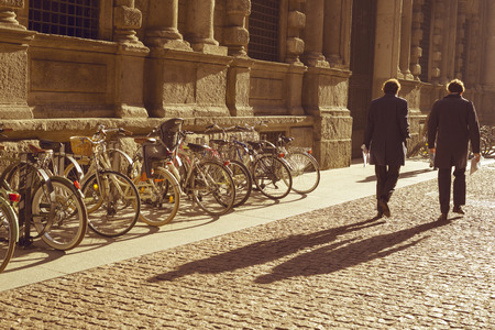 bicycle walk: MILAN - OCTOBER 22: Two men walk by cobblestone pavement along bicycle parking by sunny morning in Milan, Italy on October 22, 2015.