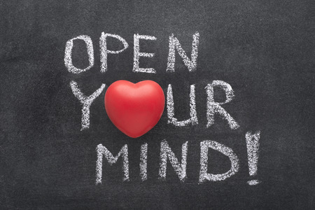 open your heart: open your mind exclamation handwritten on chalkboard with heart symbol instead of O Stock Photo