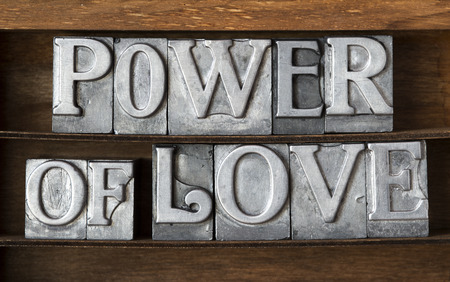 power of love phrase made from metallic letterpress type on wooden tray Stock Photo