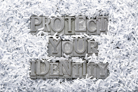 protecting your business: protect your identity phrase made from metallic letterpress type inside of shredded paper heap