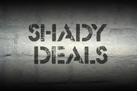 shady: shady deals stencil print on the grunge white brick wall Stock Photo