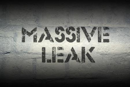 safety slogan: massive leak stencil print on the grunge white brick wall Stock Photo
