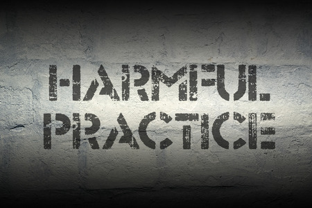 harmful practice stencil print on the grunge white brick wall Stock Photo