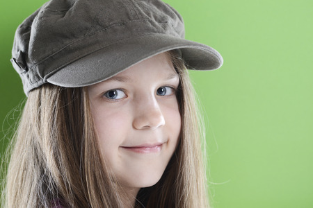 peaked: smiling girl in peaked cap with long hairs over green background