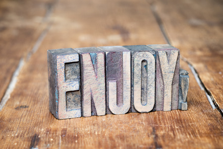 letterpress type: enjoy exclamation made from wooden letterpress type on grunge wood