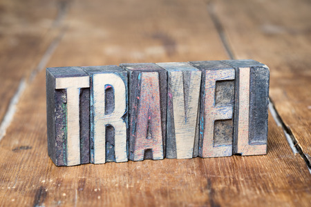 letterpress type: travel word made from wooden letterpress type on grunge wood