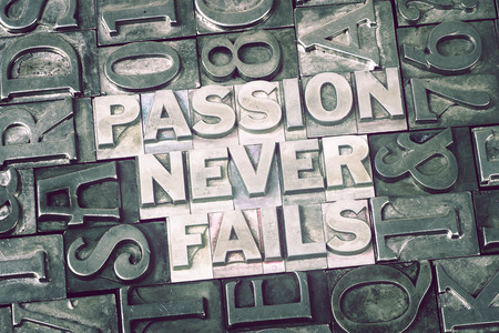 fails: passion never fails phrase made from metallic letterpress blocks with dark letters background