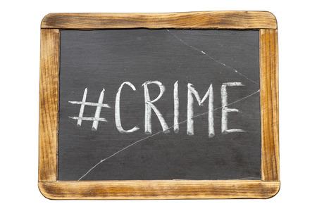chronicle: crime hashtag handwritten on vintage school slate board isolated on white Stock Photo
