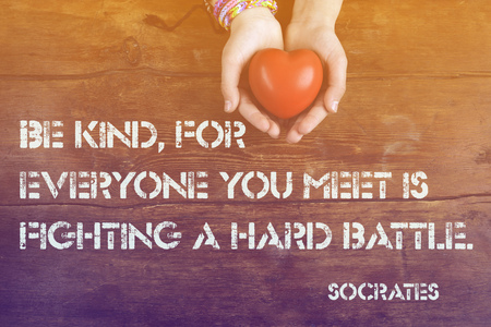 Be kind, for everyone you meet - ancient Greek philosopher Socrates quote printed on image of hahds with heart