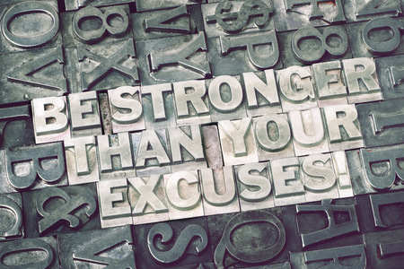 stronger: be stronger than your excuses phrase made from metallic letterpress blocks with dark letters background