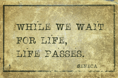 seneca: While we wait for life, life passes - ancient Roman philosopher Seneca quote printed on grunge vintage cardboard