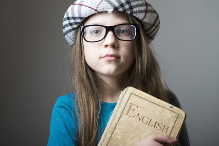 english book: serious girl in glasses and checkered hat with English book in hands