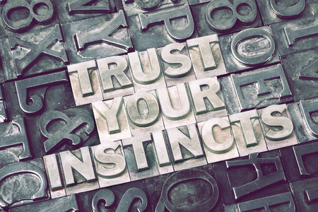 instincts: trust your instincts made from metallic letterpress blocks with dark letters background