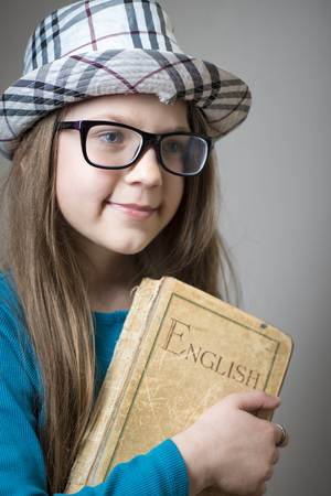 english girl: serious girl in glasses and checkered hat with English book in hands
