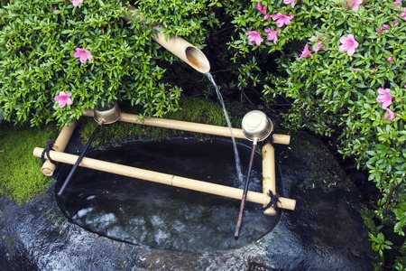 water source: traditional Japanese water basin Tsukubai fragment with bamboo pipe water source