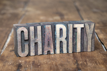 letterpress type: charity word made from wooden letterpress type on grunge wood