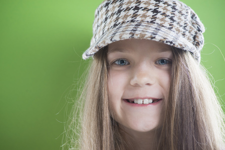 peaked: smiling girl face in peaked cap with long hairs over green background
