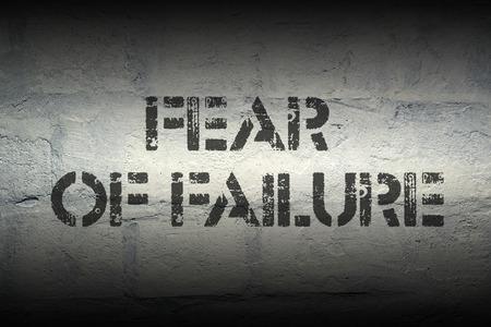 fear of failure: fear of failure stencil print on the grunge white brick wall
