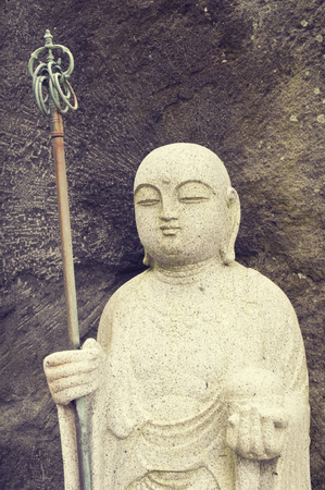 ancient japanese: ancient Japanese Buddha statue close to rocky wall