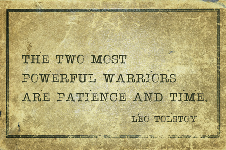 two minds: The two most powerful warriors are patience and time - famous Russian writer Leo Tolstoy quote printed on grunge vintage cardboard Stock Photo