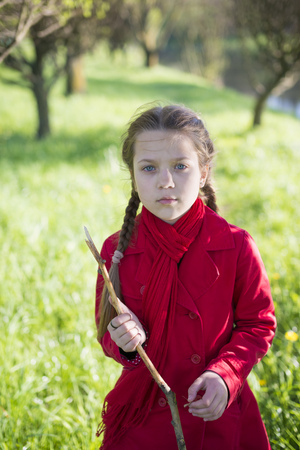wooden stick: serious girl portrait with wooden stick outdoor