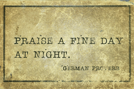 proverb: Praise a fine day at night - ancient German proverb printed on grunge vintage cardboard