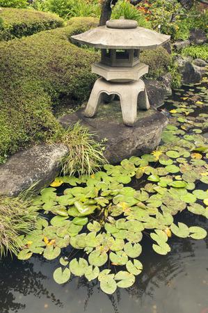 lotus lantern: ancient stone lantern structure on pond shore in Japanese zen garden by summer
