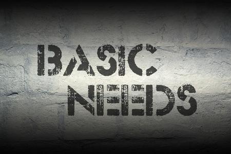 necessity: basic needs stencil print on the grunge white brick wall