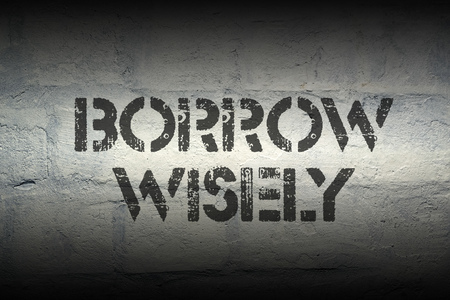 borrow: borrow wisely stencil print on the grunge white brick wall Stock Photo